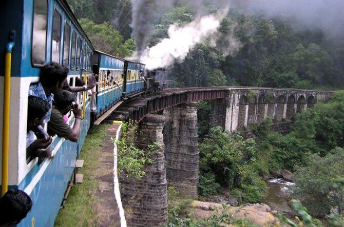 Widok boku pociągu jadącego po wysokim wiadukcie i głów pasażerów wystających z okien